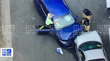 The stolen car (white) and police car crashed head-on in the Gold Coast suburb of Coomera on Thursday morning.