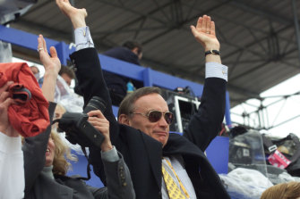 Bob Carr performs the Mexican wave at the beach volleyball at Bondi during the Olympics.