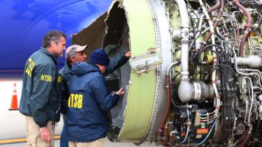 National Transportation Safety Board investigators examine damage to the engine of the Southwest Airlines plane.