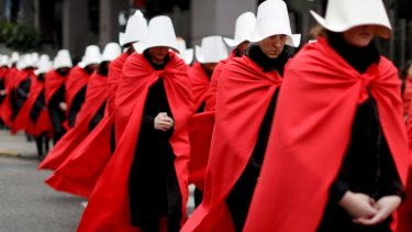 Women in favour of a measure to expand legal abortions wear red cloaks and white bonnets like the characters from The Handmaid's Tale.