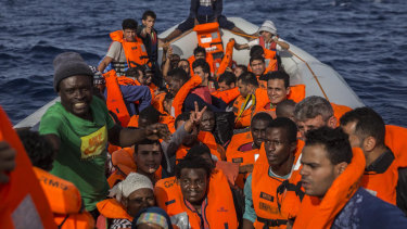 Migrants aboard a rubber dinghy off the Libyan coast are provided with life vests by rescuers aboard the Open Arms aid boat last year.