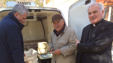 Monsignor Konrad Krajewski, right, stands with a cheese maker in Camerino, central Italy.