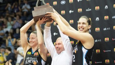 The Canberra Capitals' Kelsey Griffin, Paul Goriss, and Marianna Tolo hoist the WNBL championship trophy.