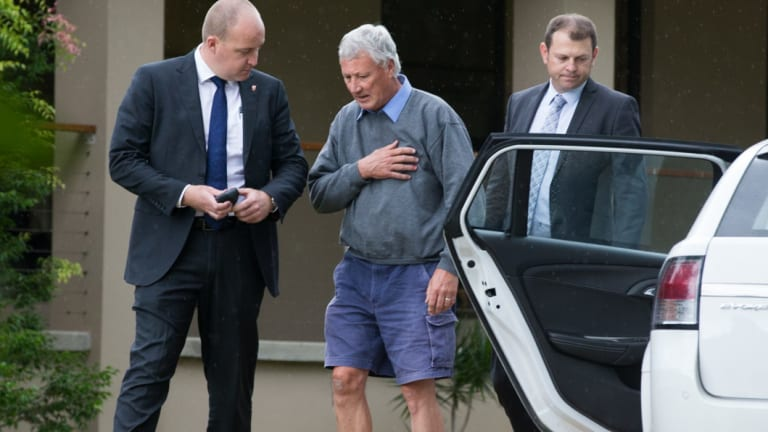 Bill Spedding, centre, is arrested at his Bonny Hills home in April 2015.