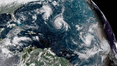 This enhanced satellite image made available by NOAA shows Tropical Storm Florence, centre, in the Atlantic Ocean on Saturday.