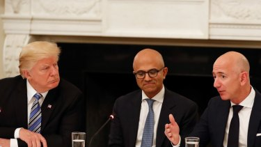 Donald Trump and Amazon boss Jeff Bezos (with Microsoft CEO Satya Nadella in the centre): The US President has repeatedly lashed out at Amazon over its tax minimisation strategy.