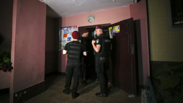 Police guard the front door of the apartment block where Arkady Babchenko was killed.