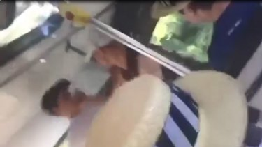 Screengrab from video appearing to show a man punching a schoolboy.