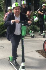 Lime director of government and policy Mitchell Price (front) scoots for joy after the company hit a million rides during its first six months in Brisbane.