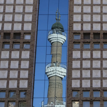 The minarets of the Urumqi International Grand Bazaar Mosque are reflected on nearby building. Taking pictures of mosques, government buildings, and police is prohibited in Urumqi, a local police officer tells us.