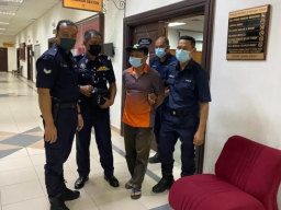 Alladin Lanim is escorted by Malaysian police during a court appearance in Kuching in August.