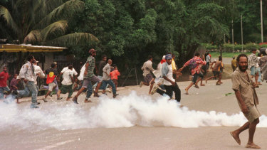 Rioters flee as soldiers disperse the crowd with tear gas and live rounds.