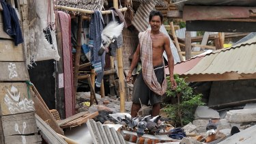 A villager feeds his pigeons among the ruins of his home in North Lombok.