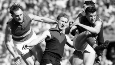 From the 1954 grand final: Bulldogs legend Ted Whitten clears the ball as Melbourne's Stuart Spencer (centre) and Geoff McGivern (partially hidden) were unable to stop him.