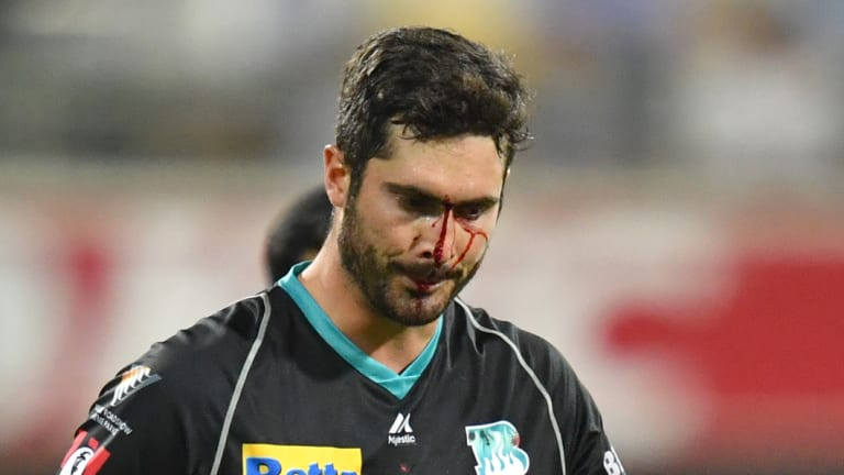 Bloodied but unbowed: Brisbane's Ben Cutting leaves the field after fielding mishap.