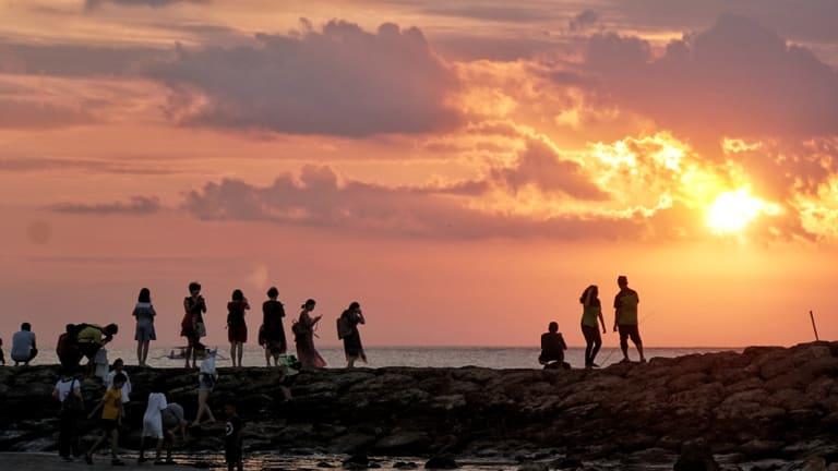 Chinese tourists watch the sunset in Kuta.