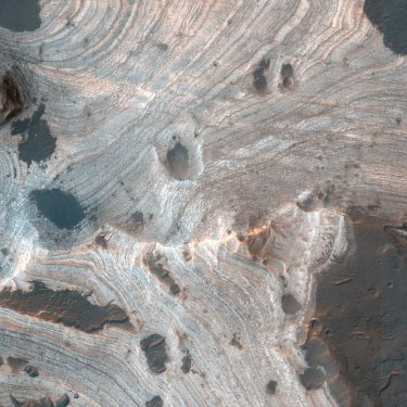 Much of Mars is covered by sand and dust but in some places, such as Holden Crater, stacks of sedimentary layers are visible.