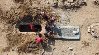 Grave diggers bury a body at Radwan Cemetery in Aden, Yemen.