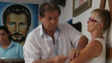 Joao de Deus, or John of God, operates on a woman's arm in 2014.
