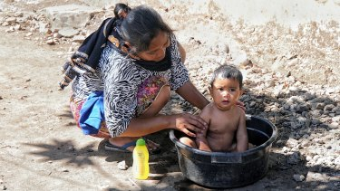 A mother bathes her daughter in a bucket after their home in Sembalun Bumbung was destroyed by the Lombok earthquake.
