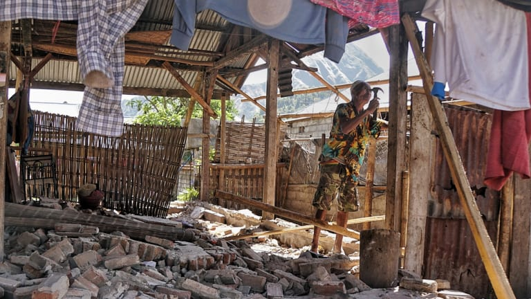Aman tries to fix a roof damaged by the earthquake in Sembalun Bumbung, east Lombok.