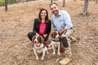 Queensland UrbanUtilitiesspokeswoman Michelle Cull with dog handler Dennis Gannaway and the star dog duo, Halo and Danny.