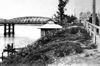 The 1910-1927 morgue on the Brisbane River bank as seen from Queen's Wharf Road, with the Victoria Bridge in the background.