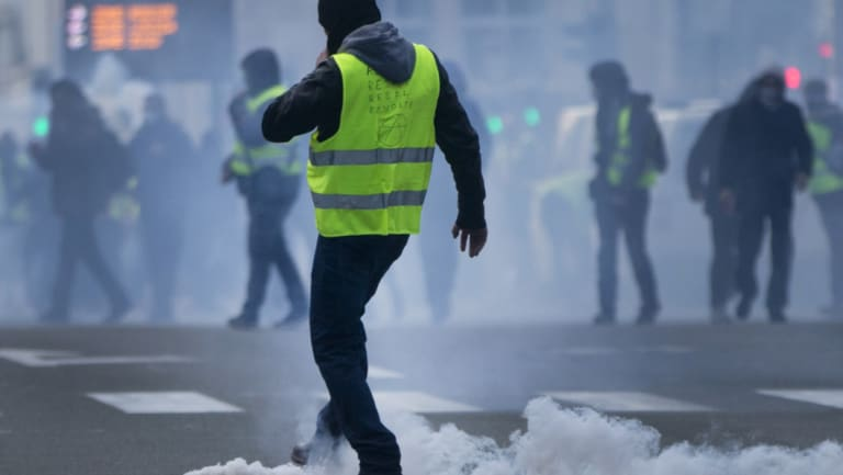 A demonstrator kicks a tear gas container back at police during a protest of the yellow jackets.