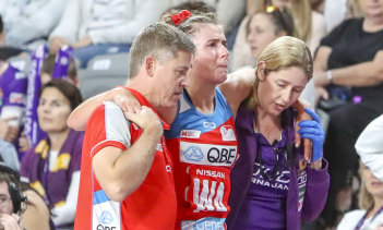 Devastated: NSW Swifts captain Maddy Proud is helped off the court on Sunday after injuring her knee.