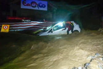 A firefighter next to a partially submerged car after heavy rains caused flooding in the town of Limone Piemonte, Italy.At least two people have died and at least 25 are missing after the storm hit France and Italy.