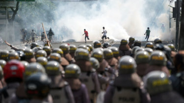 Police in riot gear, foreground, stand as demonstrators run from tear gas during a protest in Jakarta, Indonesia.