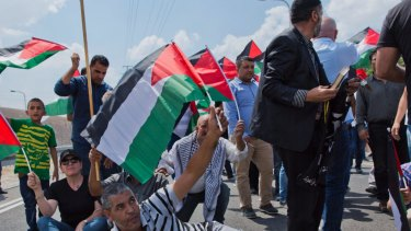 Protesters fly Palestinian flags and chant anti Israel slogans.