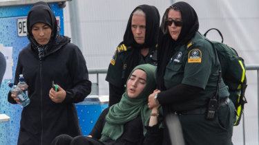 A woman is overcome at the first funeral of the 50 victims of the Mosque shootings at the Memorial Park Cemetery.