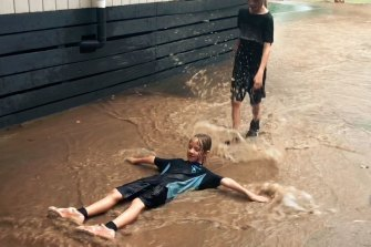 Students at Kangaroo Ground Primary School, near Eltham, playing in the rain after the school bell rang this afternoon.