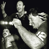 Wally Lewis is carried by Martin Bella (left) and Gene Miles after victory at the Football Stadium, 14 June 1989.