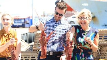 Liberal candidate for Fremantle Miquela Riley, Opposition Leader Zak Kirkup and Deputy Leader Libby Mettam handling rock lobsters at the Fremantle fishing harbour.