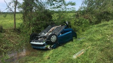 A car lies upside down in a ditch following a tornado in Franklin, Texas.