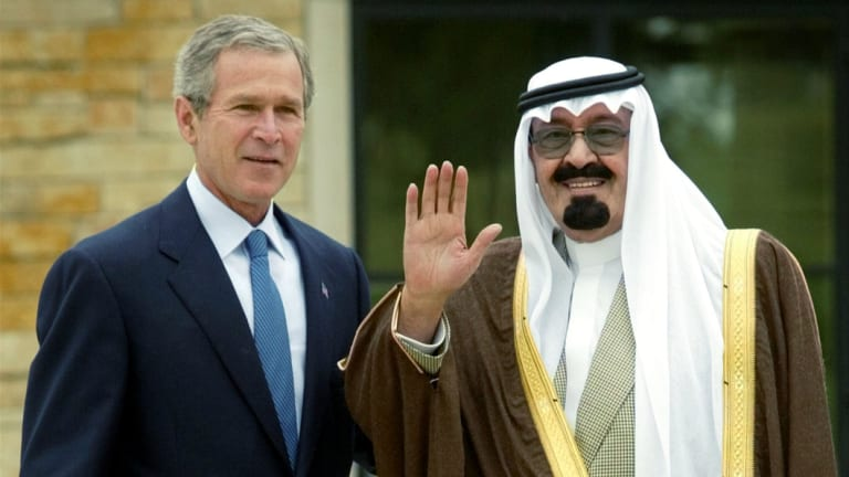 President Bush, left,  poses with a waving Saudi Crown Prince Abdullah, right, after the latter's arrival at Bush's ranch in Crawford, Texas, in 2002.