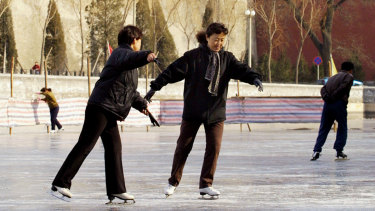 People skate on the frozen moat which surrounds Beijing's Forbidden City.