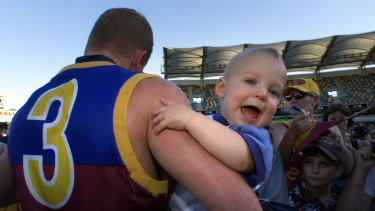 Michael Voss with his son Casey, then 1, at the Gabba.