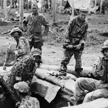 During World War II, soldiers fire a camouflaged gun during a barrage in the Solomon Islands.