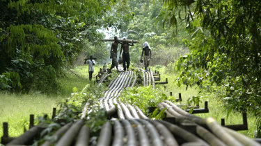 Local youths walk on an oil pipeline in Nigeria.