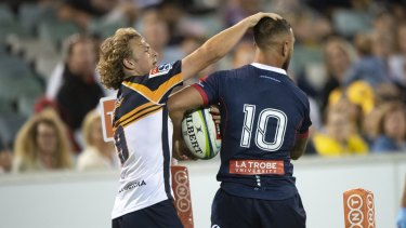 The Brumbies' Joe Powell and the Rebels' Quade Cooper exchange pats on the head as they fight for the ball.