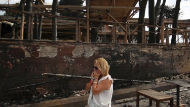 A woman stands amid the charred remains of burnt-out properties in Mati.