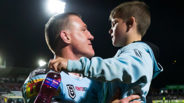 Family affair: Gallen embraces his son after the match.
