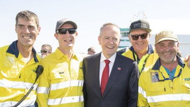 Opposition Leader Bill Shorten poses for photos with Toll workers following the official naming ceremony for Australia's newest and biggest cargo ship, Victorian Reliance II (VRII) in Port Melbourne, Sunday, February 24, 2019. (AAP Image/Ellen Smith) NO ARCHIVING
