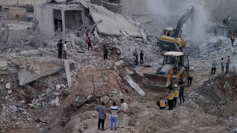 White Helmets civil defence workers and civilians inspecting damaged buildings after airstrikes hit in the village of Zardana, in Idlib province, on Friday.