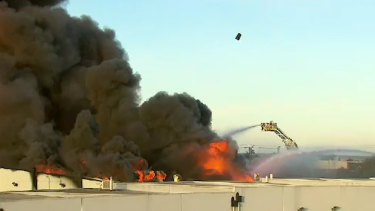 A chemical drum can be seen flying through the air above the inferno on Friday.