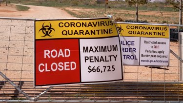 Signs warn of penalties for entering Qld from NSW at one of the many border crossings set up to keep out  COVID-19.