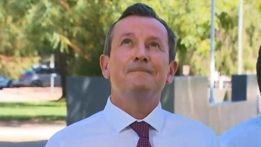 WA Premier Mark McGowan keeps an eye on a crow he dubbed 'Clive', which kept interrupting one of his press conferences during the week.